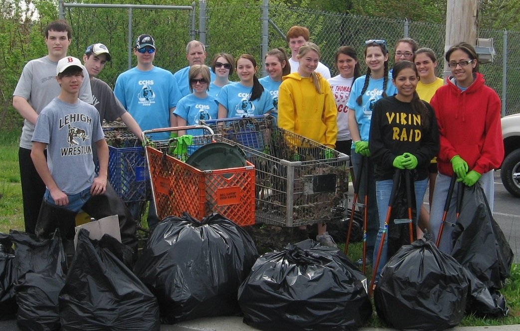 Group of teens showing how much trash they cleaned up from a park.